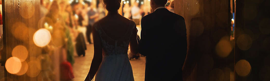 A newly married couple walking into their reception.