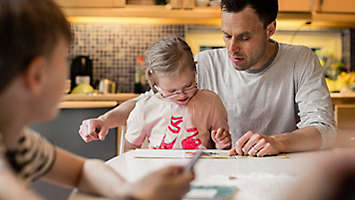 A father reading a book with his daughter at the kitchen table.