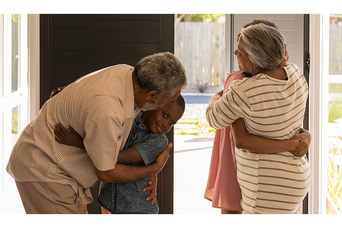Grandparents hugging their grandchildren by the front door of a house.