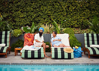 Couple expecting a baby sitting together by a pool