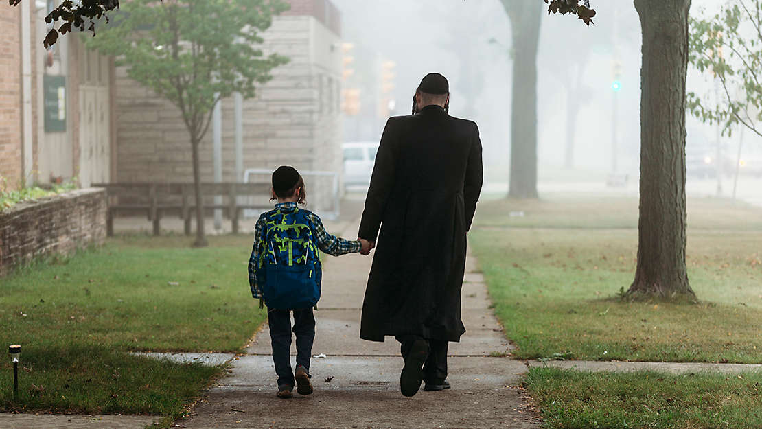 Hasidic father walking with son