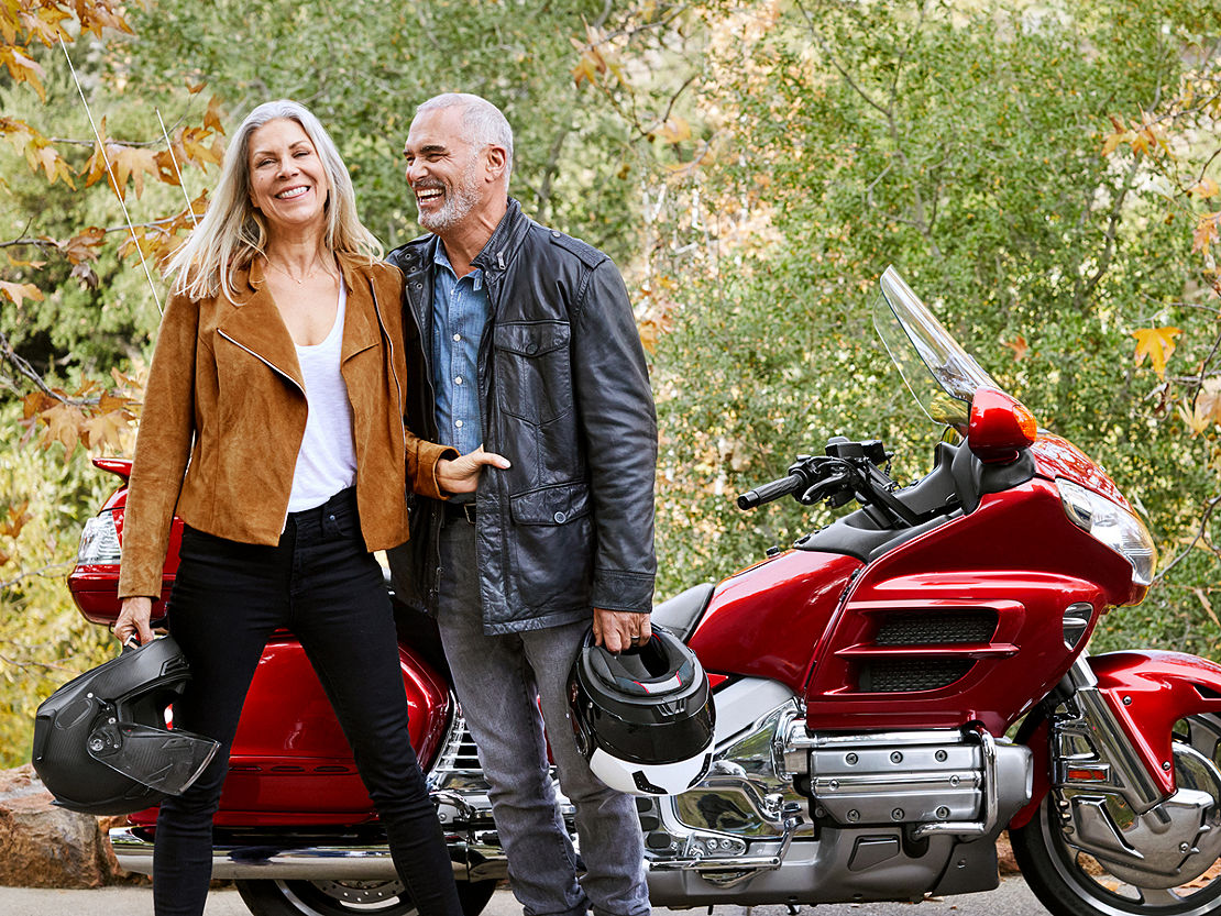 Happy retired couple outside with their motorcycle