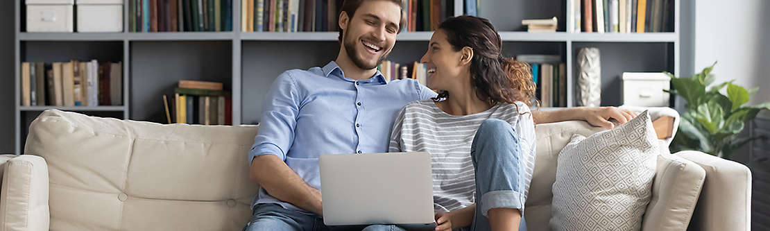man and women on couch with computer