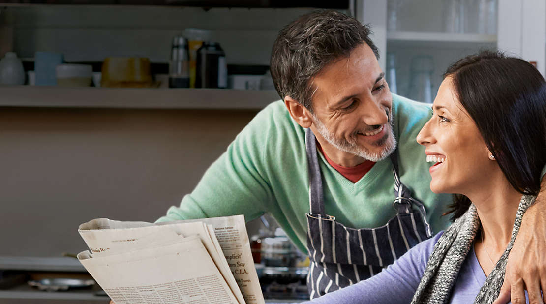 Couple in a kitchen reading the newspaper