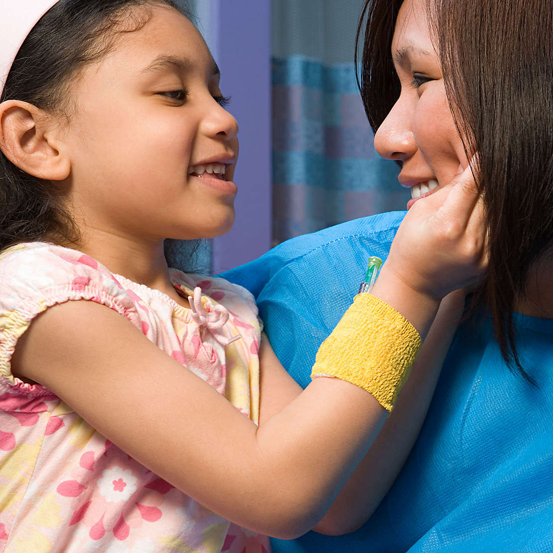Nurse holding a smiling child