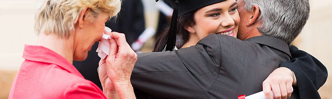 Parents hugging daughter at graduation ceremony