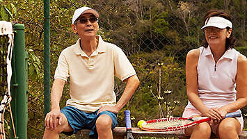 Older couple taking a break from a tennis game.
