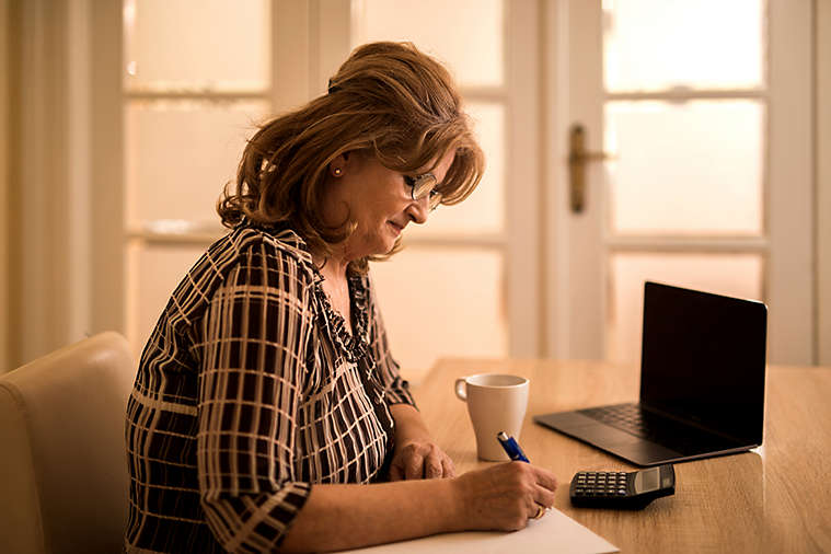 Woman sitting at table with laptop, calculator and cup of coffee.