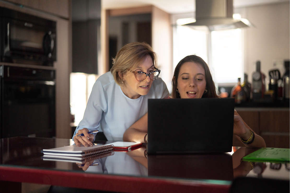 Two woman looking at laptop.