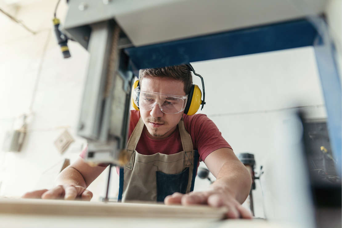 Small business owner cutting wood.