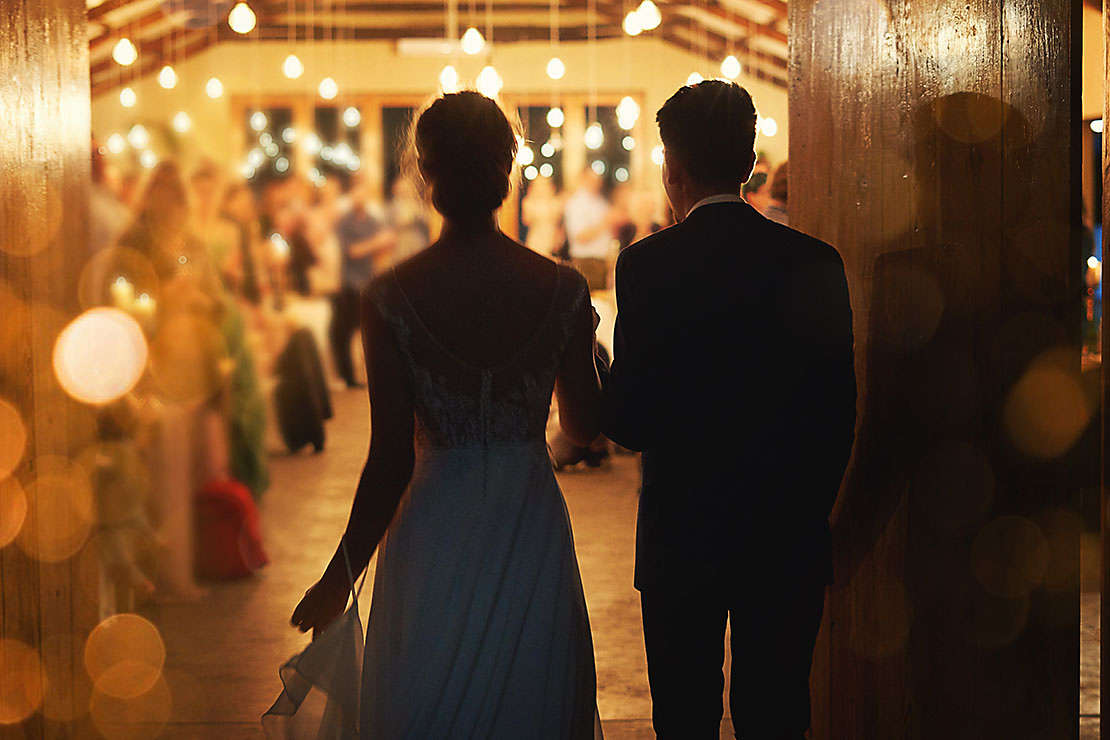Married couple walking into their wedding reception.