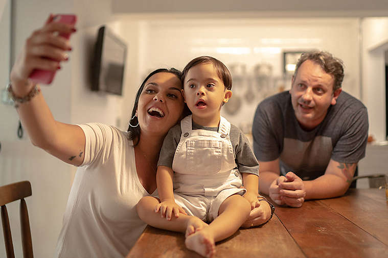 Parents taking a picture with their special needs baby.