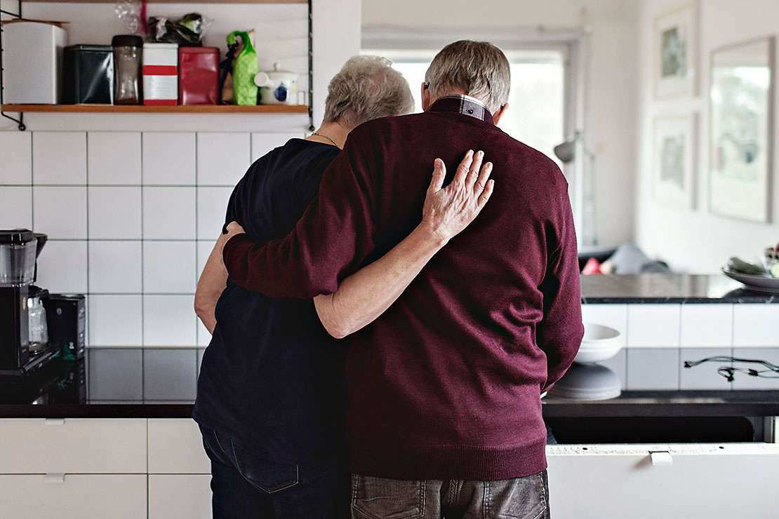 Elderly couple in their kitchen hugging each-other.