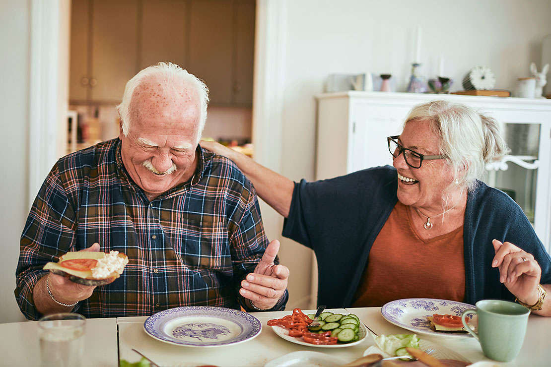 Elderly couple laughing and eating lunch in their kitchen.