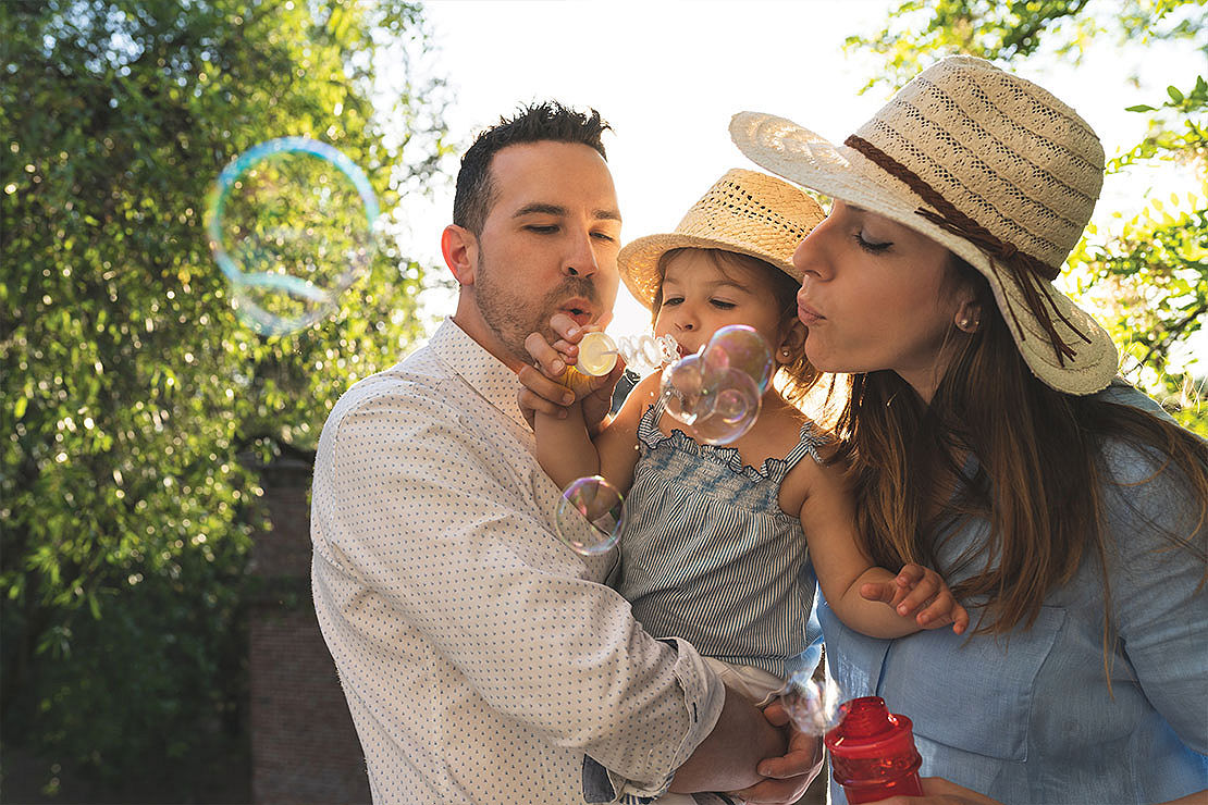 Parents with their baby blowing bubbles outside.