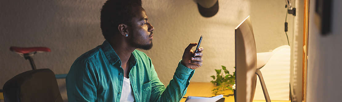 A man looking at his cell phone while working on his computer.