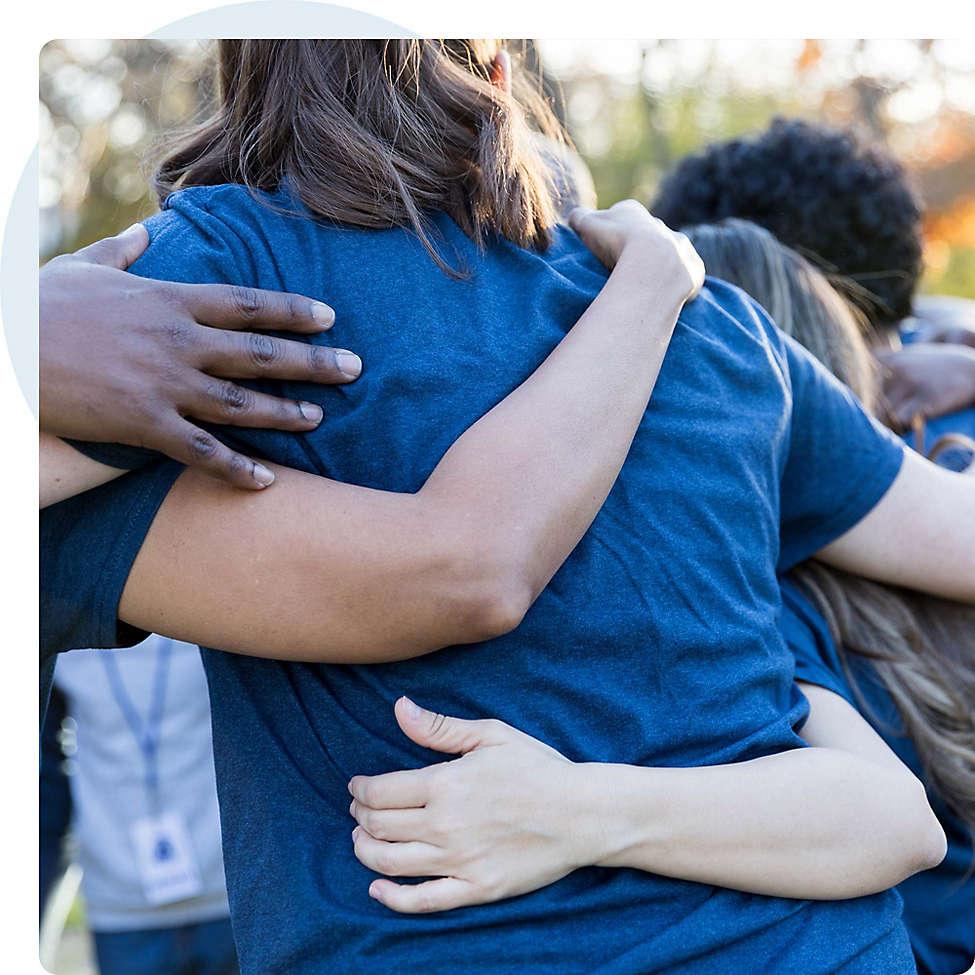 Diverse employee volunteers hugging