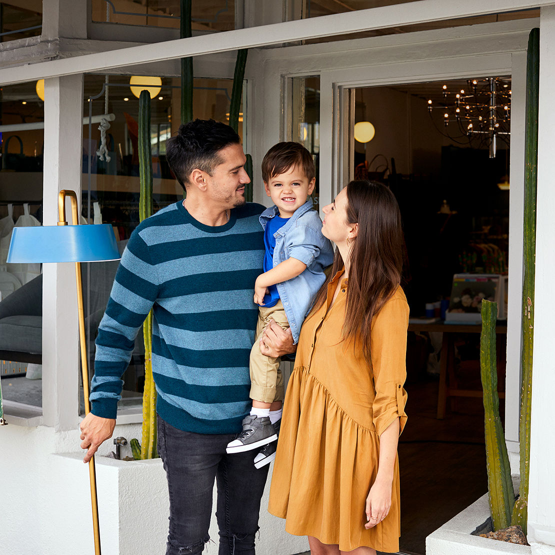 Young couple with their small child outside a shop