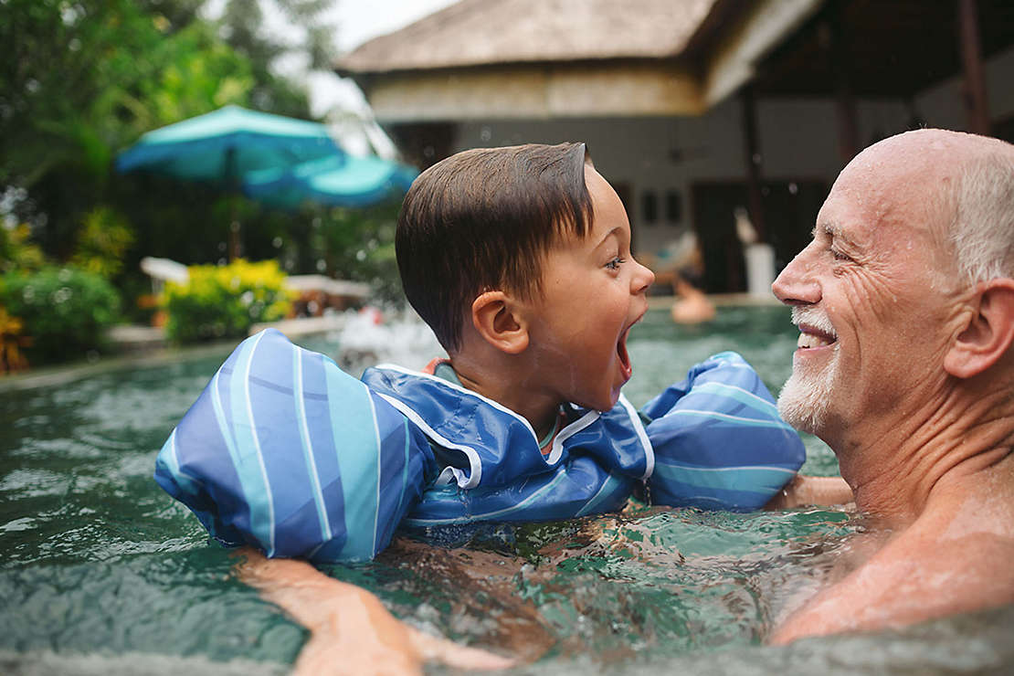 Older gentleman plays with grandchild in the pool