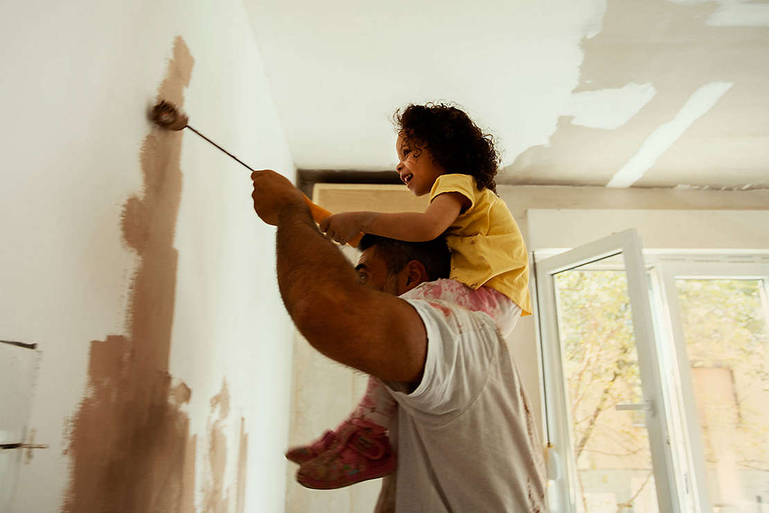 Father painting a room with his young daughter on his shoulders