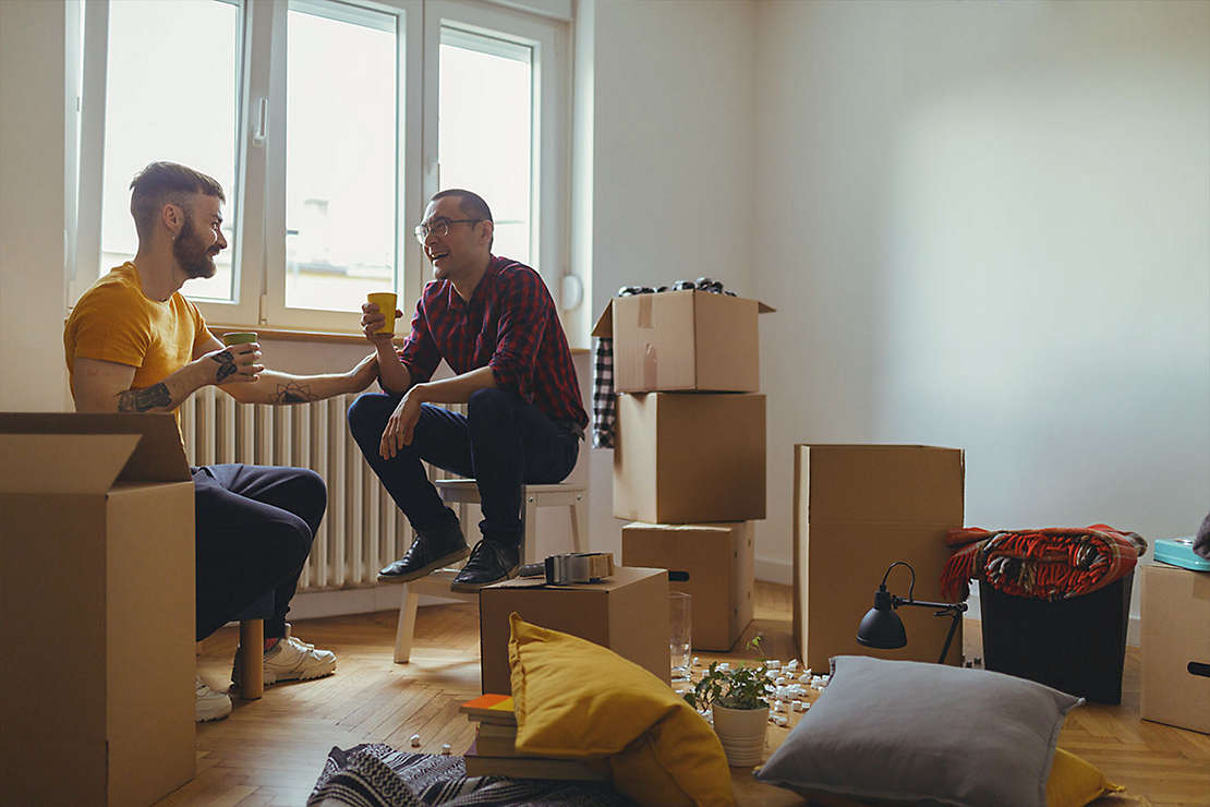2 male friends sit in room of unpacked boxes
