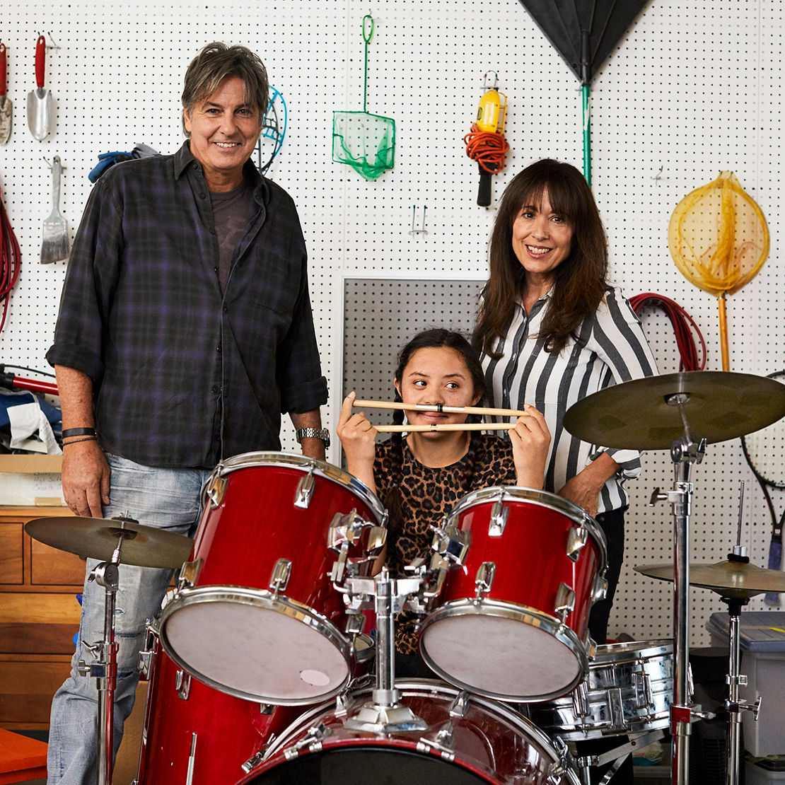 Family in their garage with their daughter and her drum set
