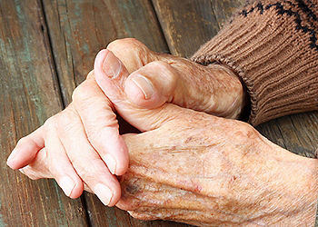 Close up view of older, clasped hands
