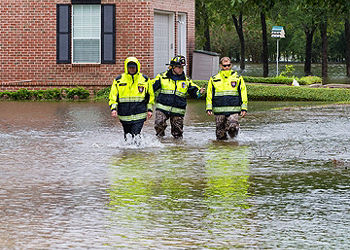 Disaster relief workers walking through a flood