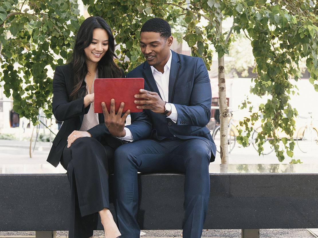 Two young employees sitting outside looking at a tablet