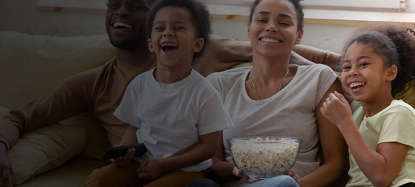 Family watches movie on couch with popcorn.