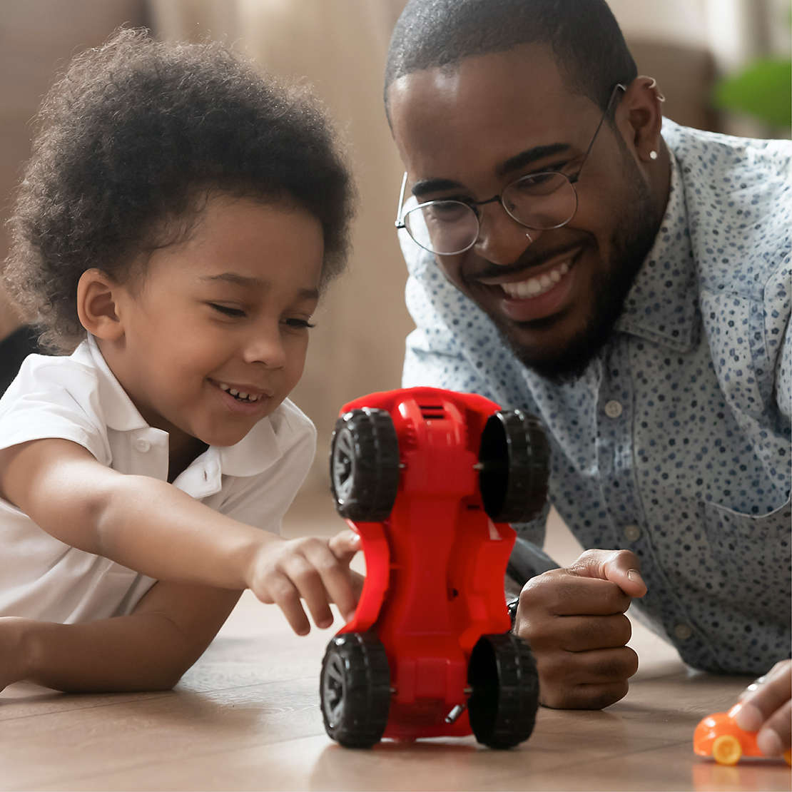 Father and son play with red race car toy
