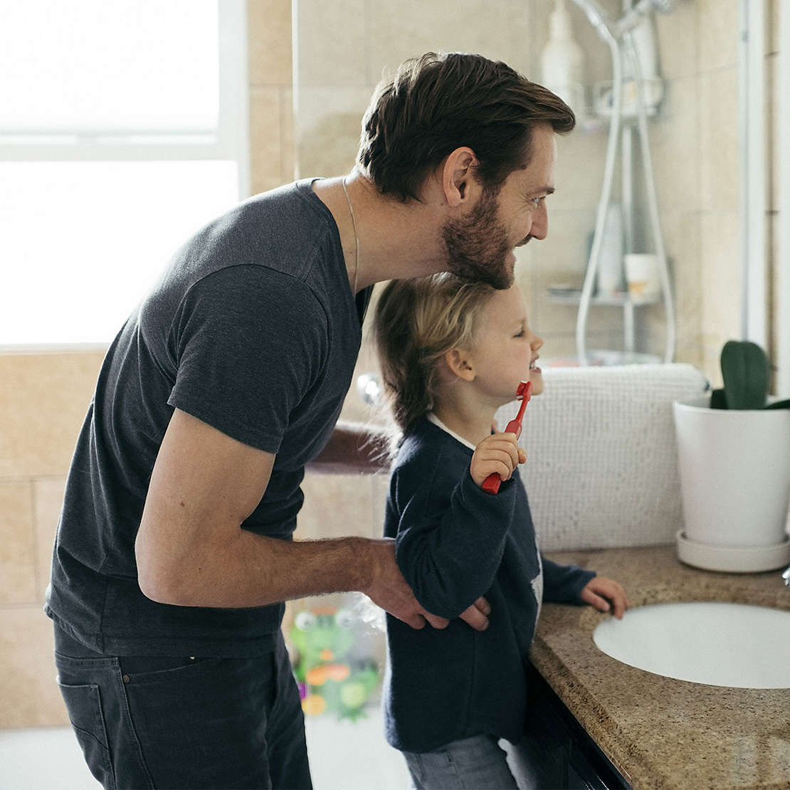 Father helping daughter brush her teeth