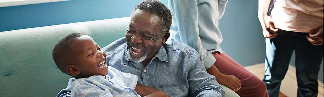 Grandfather holding grandchild smiling