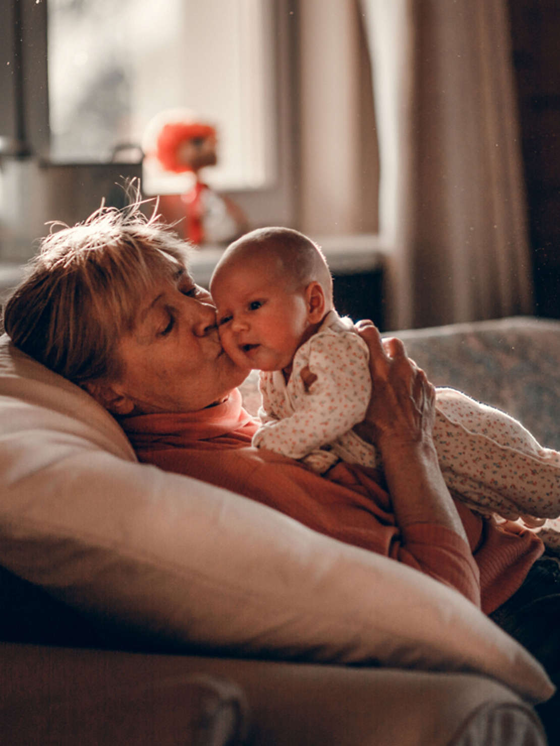 Grandmother holding grand baby on couch