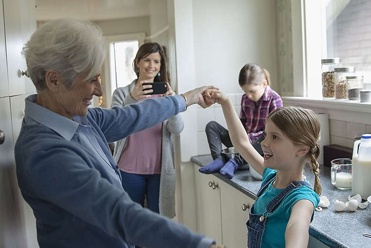 Grandmother and granddaughter dancing in kitchen