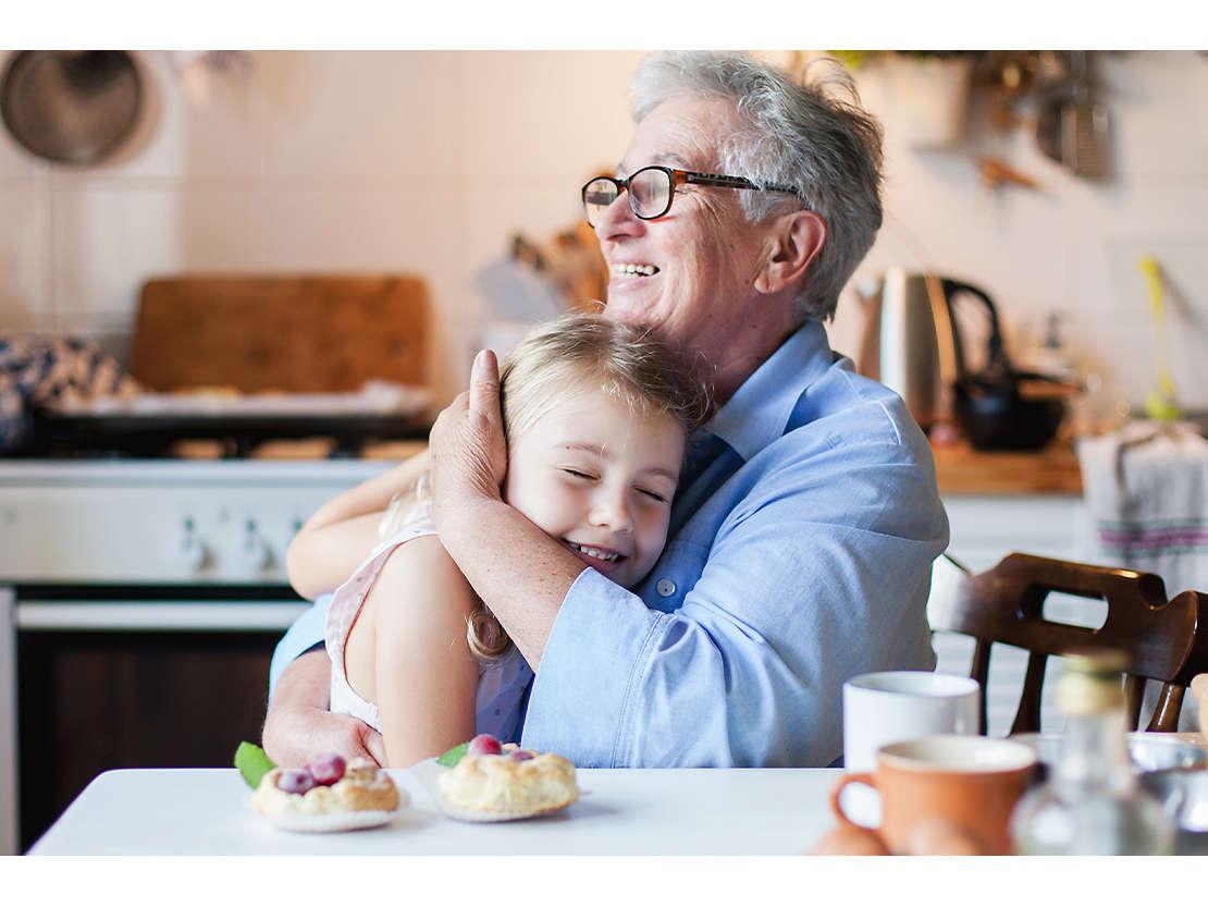 Grandmother hugging granddaughter in kitchen.