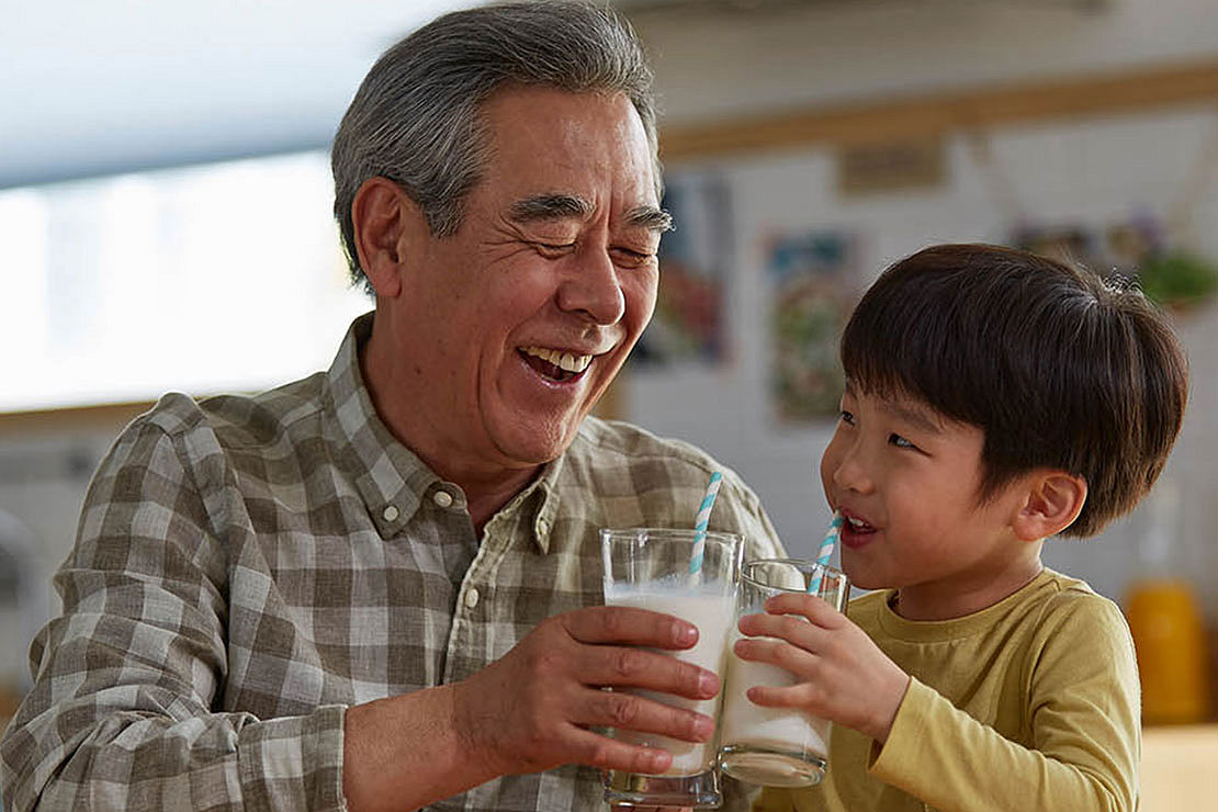 Grandson and grandfather drinking milk