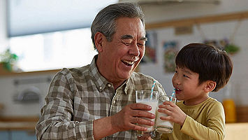 Grandson and grand father drinking milk together
