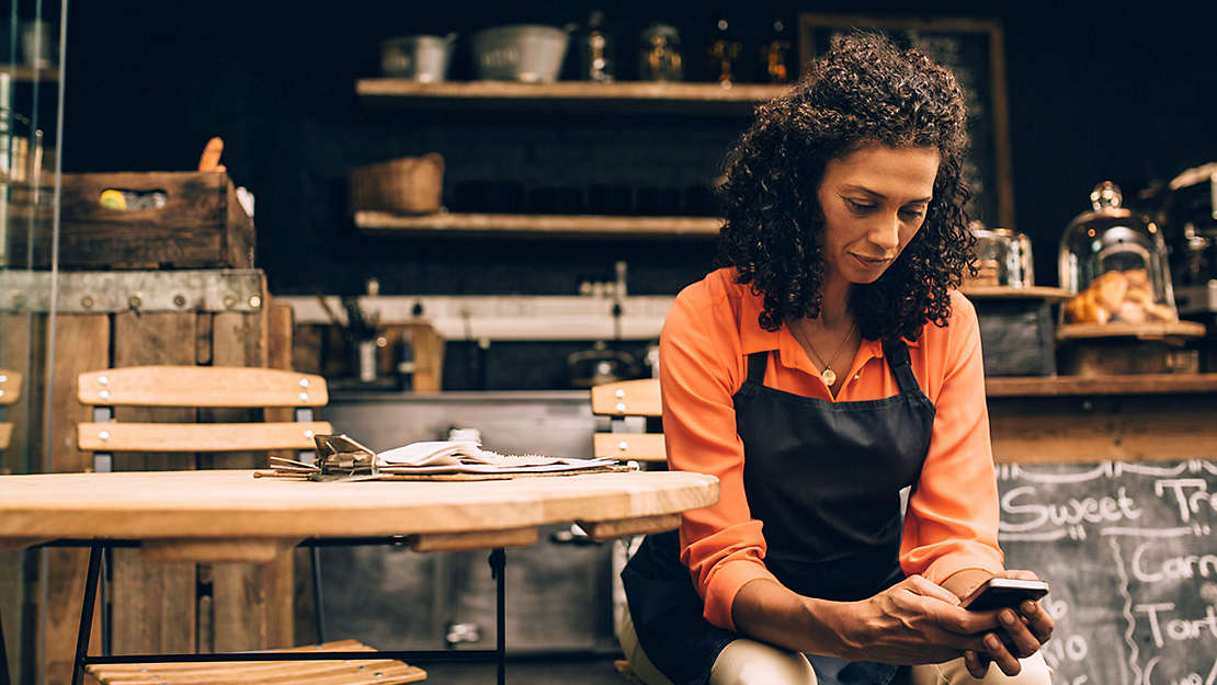 Cafe owner checking phone at a table