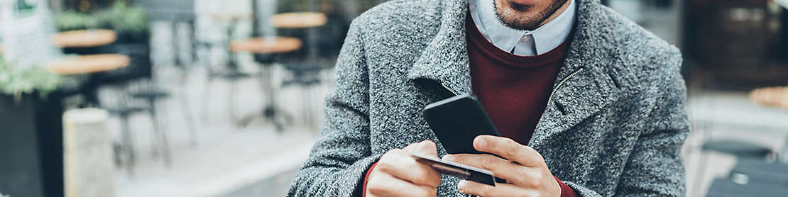 A man using his credit card while on his cell phone.