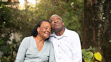 Older couple sitting outdoors among trees.
