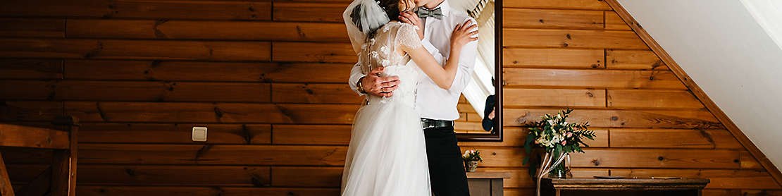 Bride and groom hugging and kissing indoors.