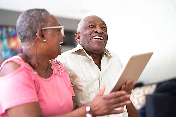 A mature couple laughing and smiling at something on a tablet.