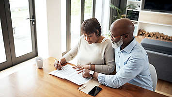 A mature couple at home sitting at a table looking over a spreadsheet.