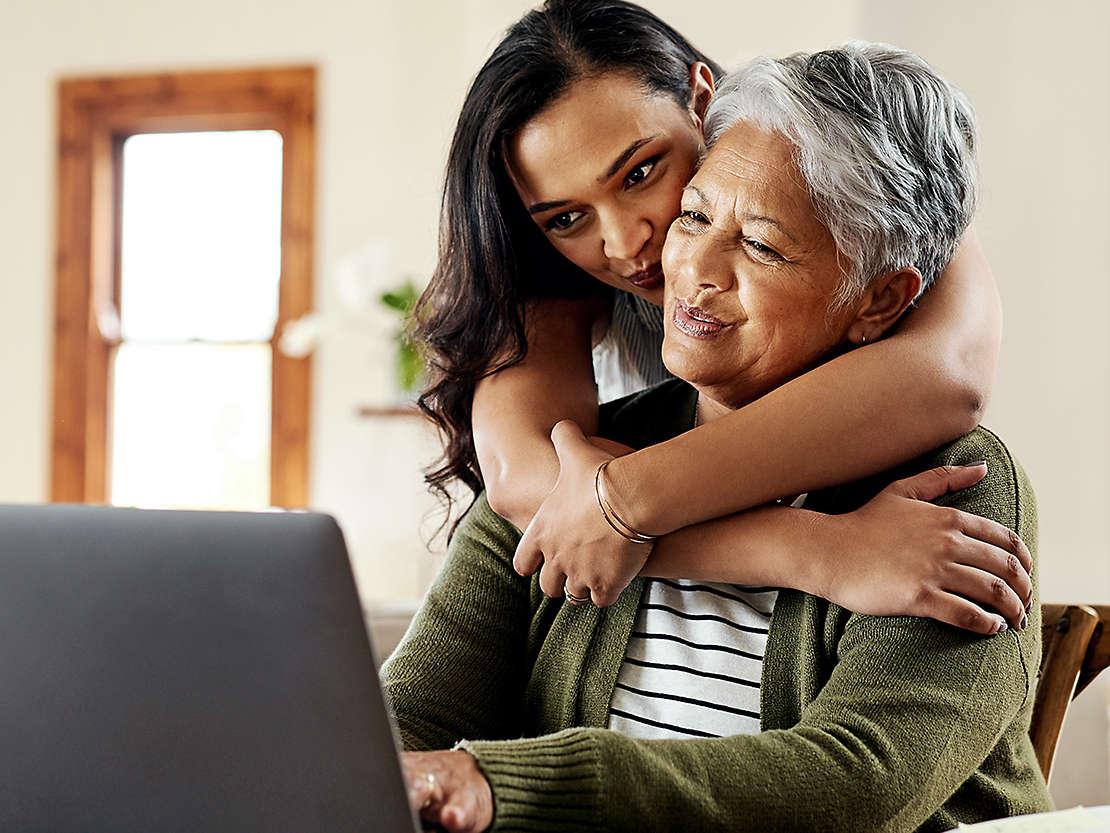 Daughter hugging grandmother at table