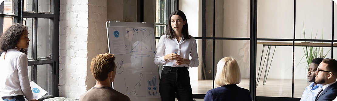 Professional presenting to a group in front of a whiteboard