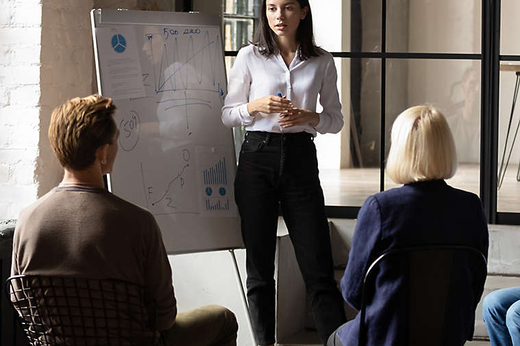 Person presenting to two people sitting down.