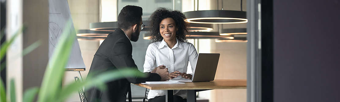 Two people talking while working on computer.