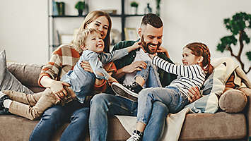 A young family playing together at home on the couch.