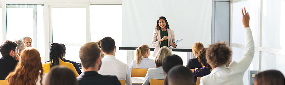 Person presenting a lecture as a student raises their hand.